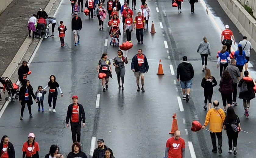 people walking on the highway including XYZ storage team wearing grey, yellow, and red