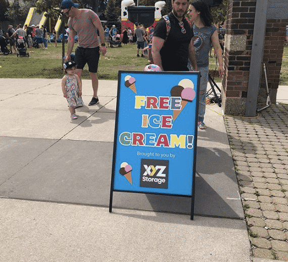 Blue Free Ice Cream sign with pictures of brown, pink and white ice cream scoops and colourful text