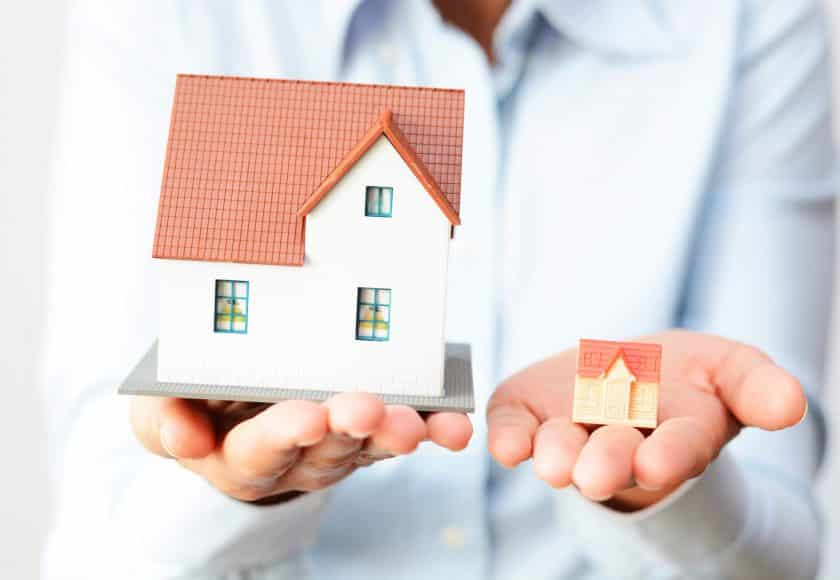 person holding big house in left hand and small house in right hand