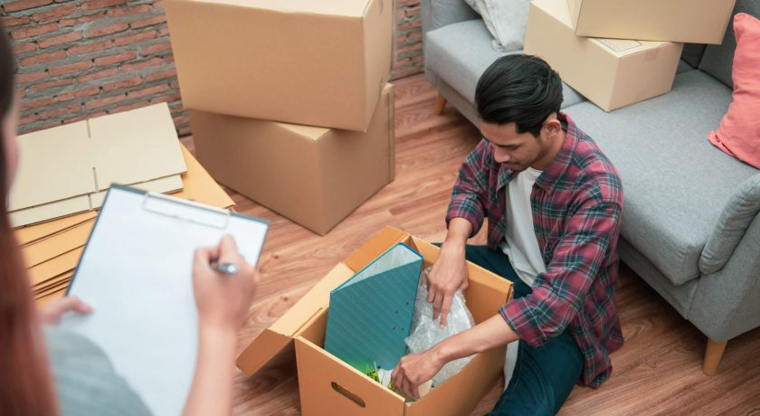 Young Asian couple packing their belonging into cardboard box by using a check list before moving to new resident or house after buy or rent a new one.