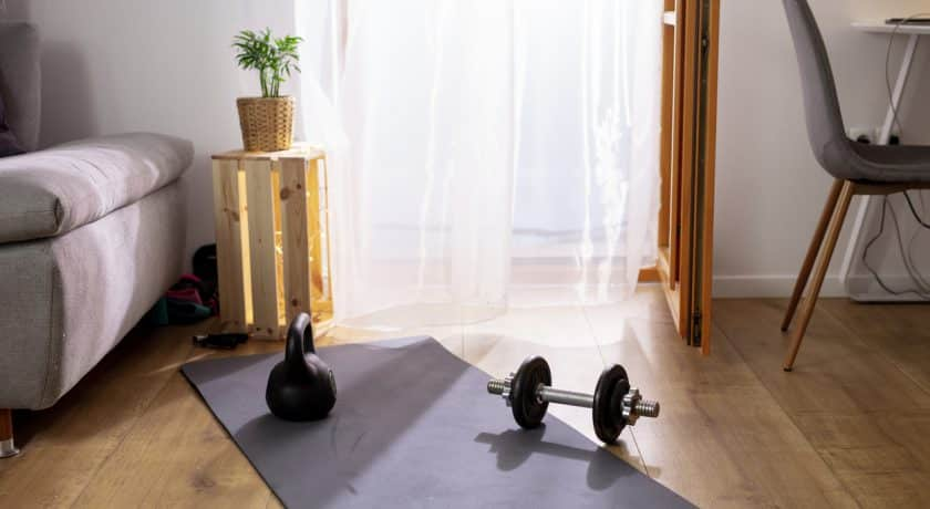 Kettlebell and weights on yoga mat in living room