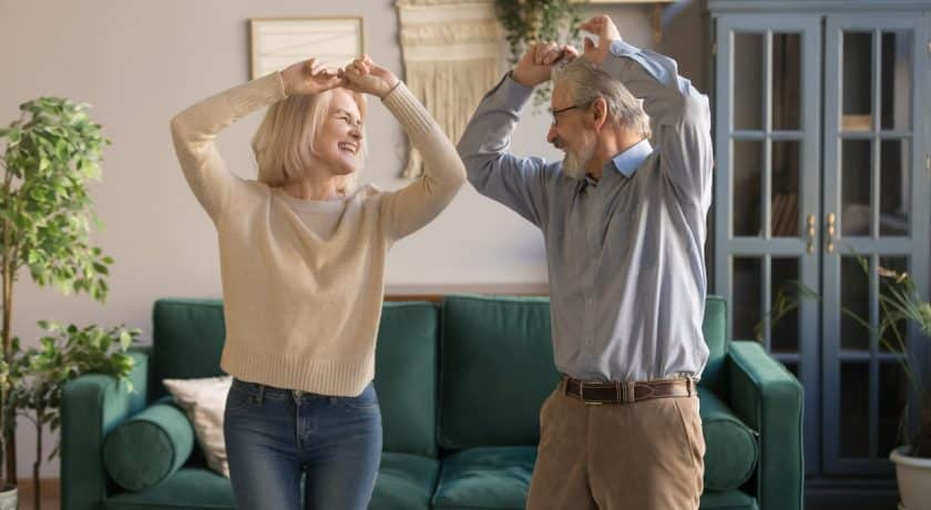 Funny sixty years old couple in love having fun at home, elderly spouses standing raised hands dancing feels carefree healthy enjoy active weekend, do exercises well being of retirees people concept