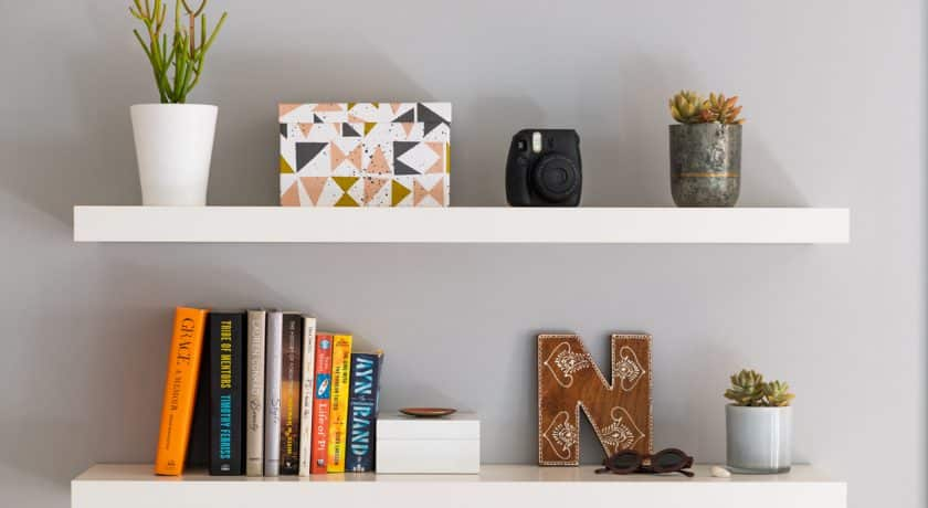 Two white painted modern bookshelves with books, plants, a decorative storage box and personal items.