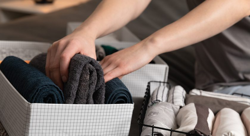 Vertical storage of clothing.Women organize clothes in a modern bedroom. Women sorting clothes in baskets room cleaning concept.