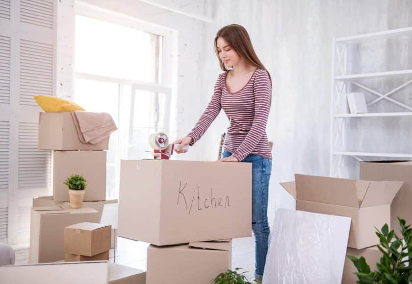 Ready to move. Pretty dark-haired girl taping the box with kitchen cutlery while packing her belongings before moving out of the apartment