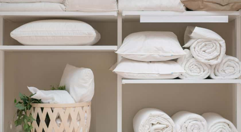 Various household items such as pillows and quilts standing in the white cupboard in the laundry room.